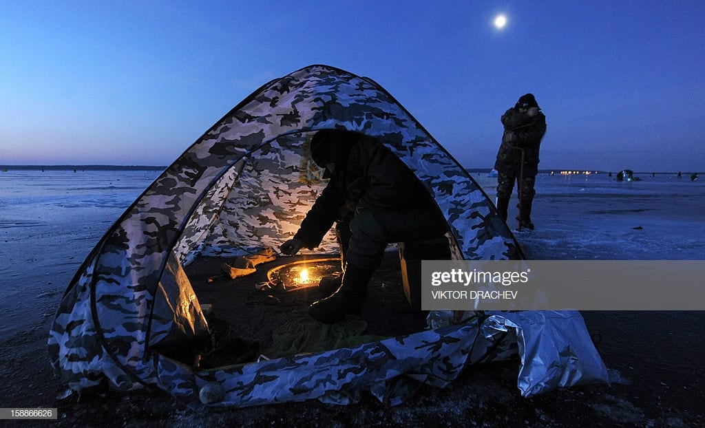A Man Sits In A Tent While Ice Fishing At Sunrise In The Lake Vileika Near The Belarus Village Of Kasun, Some130 Km North Of The Capital Minsk Early On January 2, 2013. AFP PHOTO / VIKTOR DRACHEV        (Photo Credit Should Read VIKTOR DRACHEV/AFP Via Getty Images)